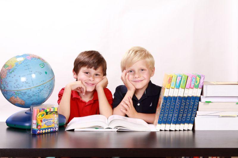 Zwei Jungs sitzen mit Schulmaterial an einem Tisch
